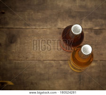 Two bottles of apple juice on an old rustic barn wood background view from above