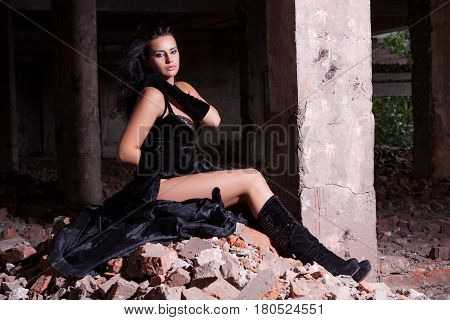 Young beautiful woman posing in ruins after fire