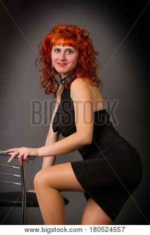 Beautiful young red-haired girl in a black dress on a gray background