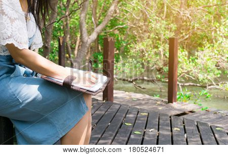 Lady travel Ecotourism Write down the information notebook in the wood Golden Meadow Prong thailand