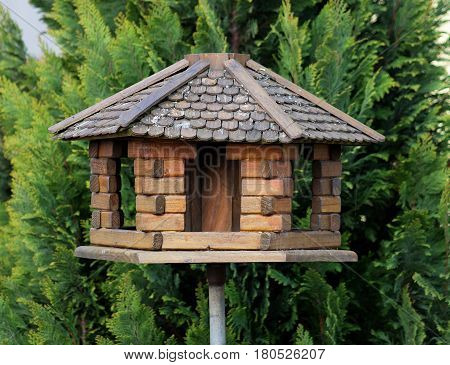 nice and small handcrafted wooden bird feeder with wicker roof