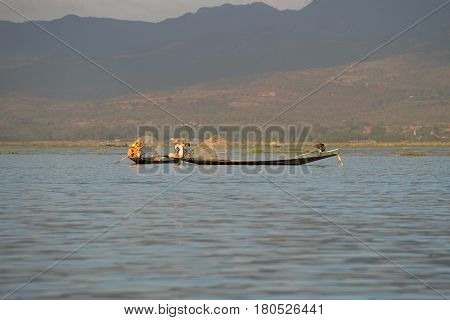 INLE LAKE, MYANMAR - DECEMBER 26, 2016: The having a rest fishermen on the Inle lake in the evening light