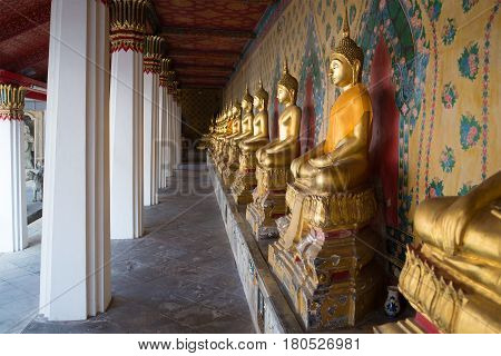 BANGKOK, THAILAND - JANUARY 24, 2014: Gallery with antique sculptures of the seated Buddha in the Buddhist temple Wat Arun