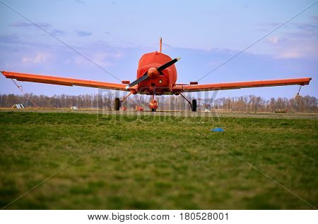 Small aircraft with a propeller in the parking lot of the airfield.