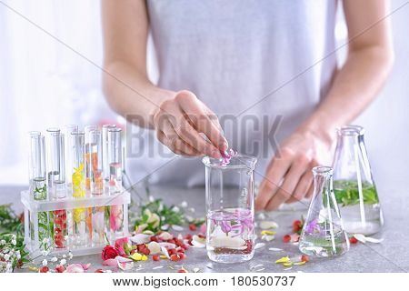 Woman mixing perfume samples on table