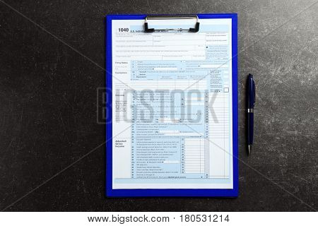 Clipboard with individual tax return form on gray background