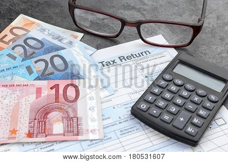 Tax return form, glasses, calculator and euro on table