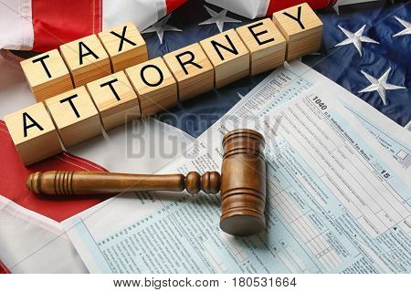 Wooden cubes with space for text, judge gavel and tax forms on American flag background