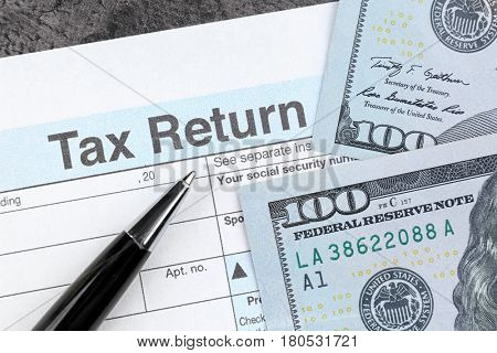 Tax return form, pen and dollars on table