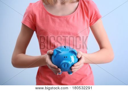Cute girl with piggy bank on color background, closeup