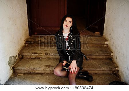 Young Goth Girl On Black Leather Skirt And Jacket Posed On Stairs Of Old House.