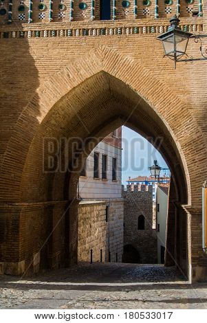 An archway of a mudejar style tower old buildings and a lantern at the wall at medieval town Teruel at Aragon province Spain.