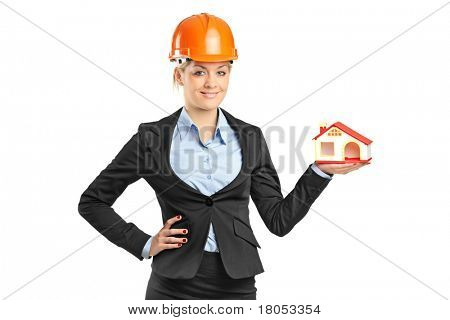 A smiling blond forewoman holding a model house isolated on white background