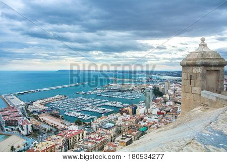 A view from Santa Barbara Castle at the hill in the center of Alicante to a port of the city with a plenty of yachts to roofs of the buildings and to Mediterranean sea on cloudy day Alicante Spain.