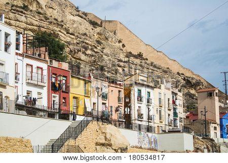 ALICANTE SPAIN - FEBRUARY 12 2016: Bright colored traditional houses at Barrio Santa Cruz a district near Santa Barbara castle Alicante Spain.
