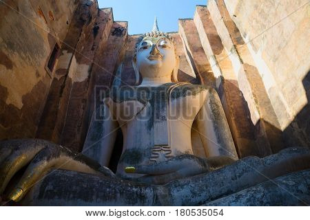 Giant sculpture of a seated Buddha on the ruins of the ancient Buddhist temple of Wat Si Chum. Sukhothai, Thailand