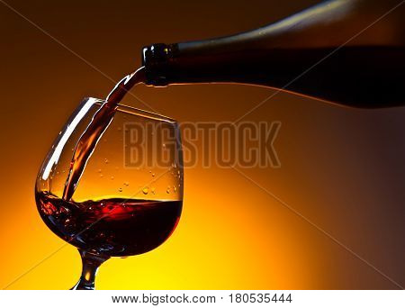 Brandy Poured Into A Glass On A Yellow Background