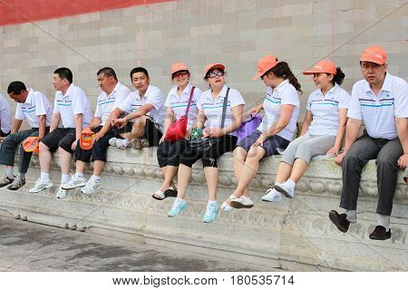 Asian tourists sitting and taking break on a low wall in Forbidden City the Palace Museum north of Tiananmen Square. Beijing China 18.june 2010