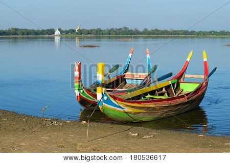 Two colored traditional Burmese boats on the shore of Taung Tha Man lake. Amarapura, Myanmar