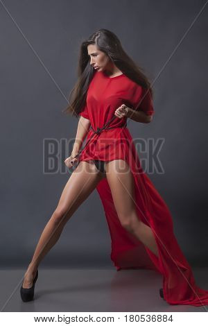 Beautiful girl in a red dress posing in the studio