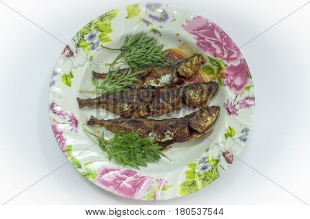 Fried fish with sambal belacan and vegetable side dish.Fried fish with sambal is a popular home-style dish in Malaysia,Singapore,Indonesia & Thailand.