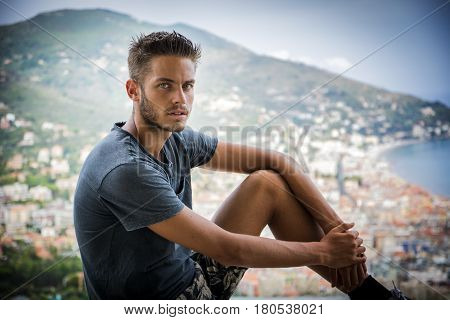 Handsome Young Man in Trendy Attire, in a Sunny Summer Day with Italian Sea Coast in the Distance, Wearing a White Shirt