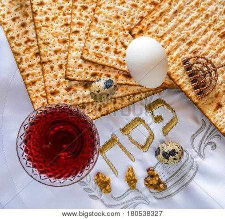 Jewish Passover celebration concept with glass of red wine, walnut, unleavened bread (matzoth) and napkin with Hebrew letters - pesah