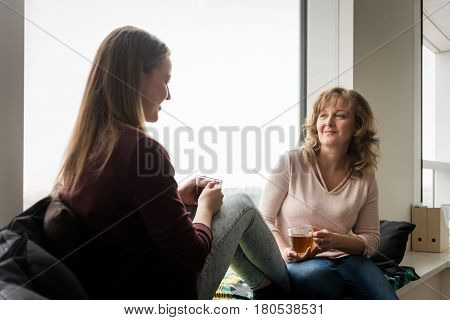 Mother talking to her daughter while having tea at home