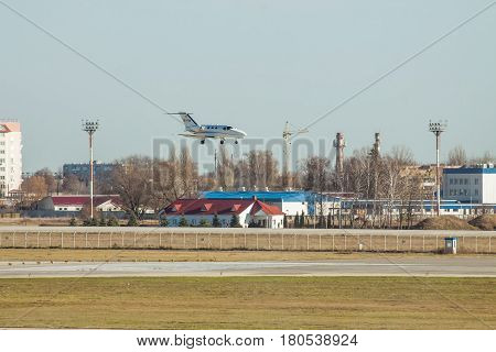 Kiev Region Ukraine - November 13 2011: Cessna 510 Citation Mustang is landing in the airport with some industrial buildings on the background
