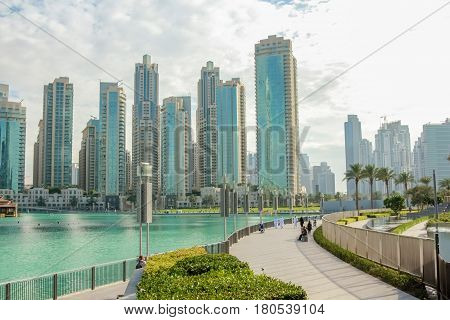 People walking along the waterfront promenade that runs along the Burj Khalifa Lake and the Burj Khalifa. On background, the Old Town Island and the Dubai Mall in Downtown Dubai.