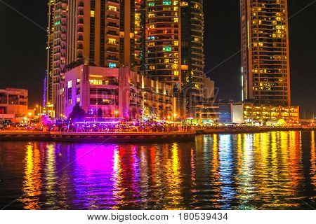 Dubai Marina Walk illuminated at night. Dubai Marina is a newly futuristic district, famous for restaurants, luxury clubs, and nightlife.