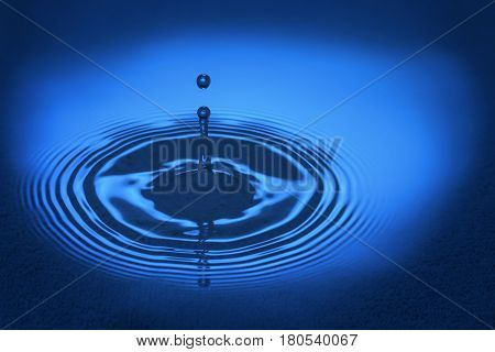 stiffened water drop falling on a water surface,Blue tone