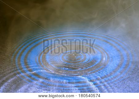 stiffened water drop falling on a water surface ,In smoke with reflection