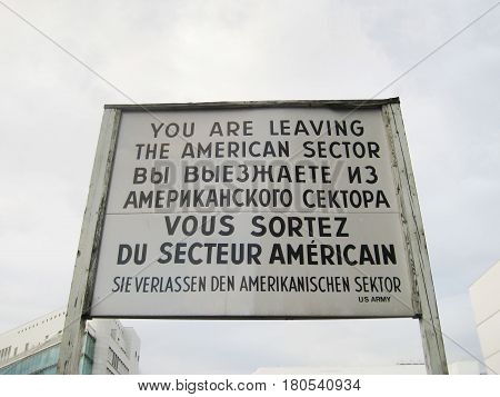 BERLIN, GERMANY - JULY 20, 2016: Famous historical  sign at former East West Berlin border. Former Checkpoint Charlie, old sign with warning of leaving the american sector during World War 2, Cold war