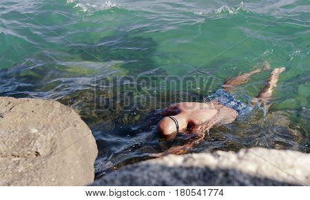 a man floating facedown on the water looking for sea-hedgehogs in Paralia Katerini, Greece