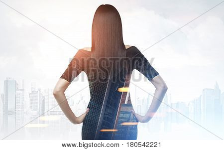 Rear view of businesswoman wearing a black dress and standing with her hands on the waist looking at a gray city panorama. Toned image. Double exposure. Mock up