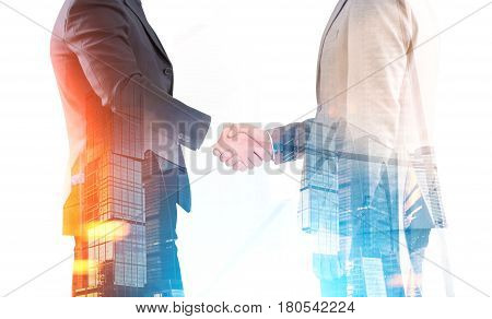Close up of two businessmen shaking hands while standing against a morning city background. Toned image. Double exposure