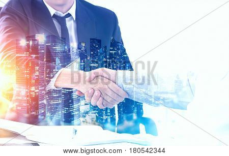 Close up of two business partners shaking hands at a table. There is a night city panorama in the foreground. Toned image double exposure.