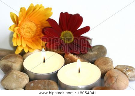 Spiritual and indulgence : Two candles surrounded by shiny pebbles on white plate decorated by a yellow and red flowers, isolated