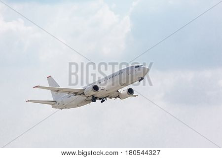 white plane takes off from the runway on the background of houses