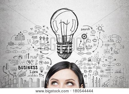 Close up of a head of a black haired woman standing near a concrete wall with a business idea sketch drawn on it.