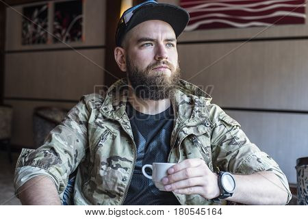A Bearded Guy. The Guy With A Cup Of Coffee.