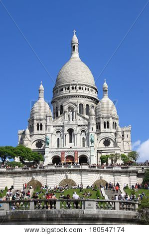 PARIS FRANCE - MAY 24: Basilica of the Sacre Coeur on May 25 2015 in Paris France. The Basilica of the Sacre Coeur is a roman catholic church located at the top Montmartre hill the highest point in Paris