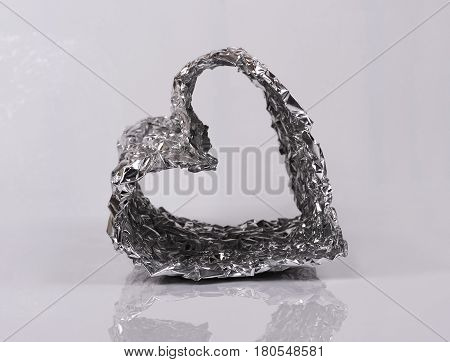 silver foil heart shaped with reflection, closeup
