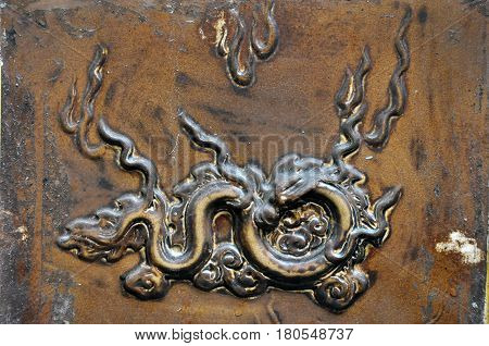 Bas relief carved brass detail on a bronze backgrounf