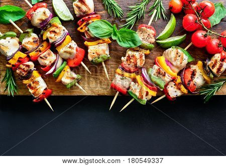 Chicken or turkey and vegetables cooked spicy skewers put on a board ready to be served as summer party meal view from above space for a text