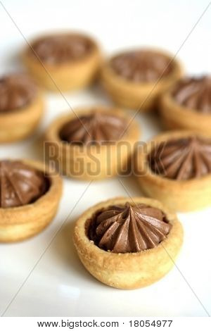 A spread of small pastry cased chocolate pie with ganache topping