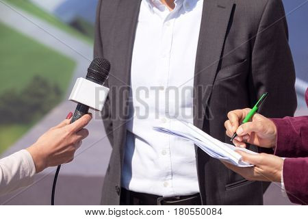 Reporters conducting press interview, holding microphone, writing notes