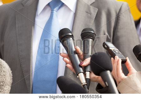 Journalists holding microphones conducting media interview. News conference.