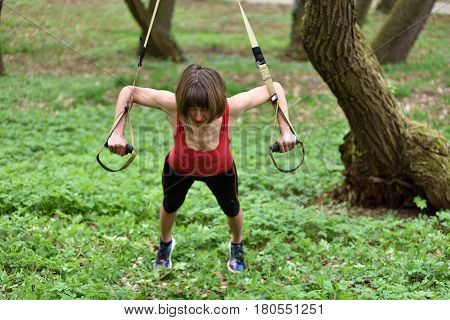 Young Woman Does Suspension Training With Fitness Straps In The Outdoors